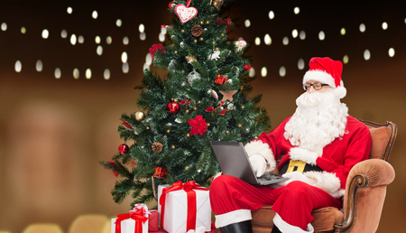 man in costume of santa claus with laptop Stock Photo