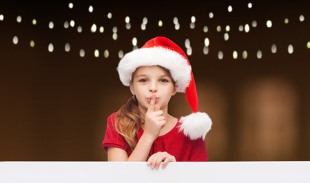 girl in santa hat with board making hush gesture Stock Photo