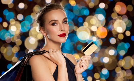 クレジットカードとショッピングバッグを持つ女性
