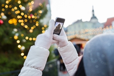 hands with smartphone photographing christmas tree