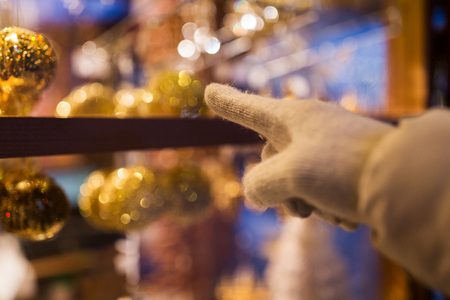 hand pointing at christmas toys behind shop window