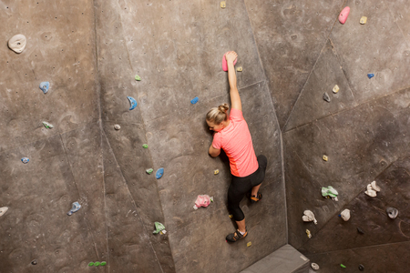 young woman exercising at indoor climbing gym Stock Photo - 87979272