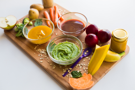 many babies: vegetable puree or baby food in glass bowls