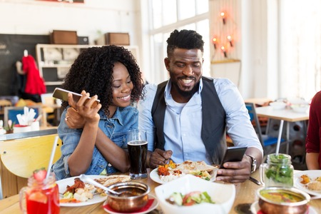 happy man and woman with smartphones at restaurant