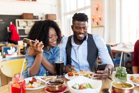 gelukkige man en vrouw met smartphones bij restaurant Stockfoto