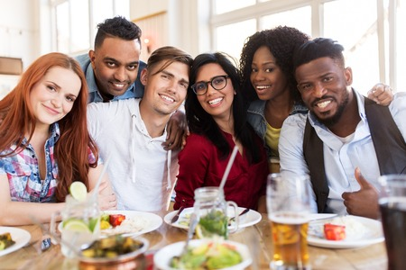 happy friends eating at restaurant Stock Photo - 87979096