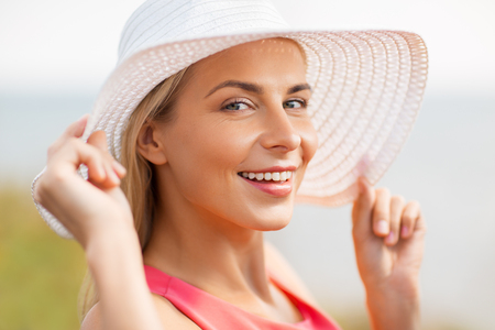 portrait of beautiful smiling woman in sun hat