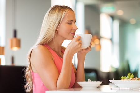 woman eating and drinking coffee at restaurant Stock Photo