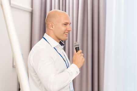 businessman with microphone at business conference