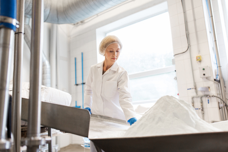 woman working at ice cream factory conveyor Archivio Fotografico