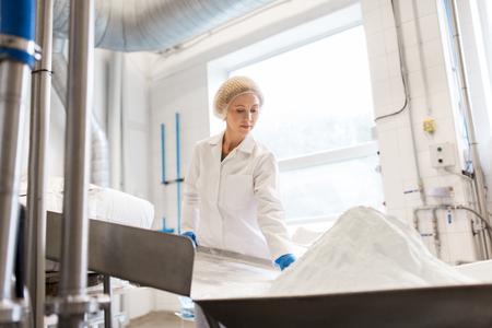 Vrouw die werkt bij de transportband van de roomijsfabriek Stockfoto - 87979119