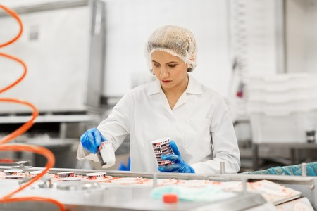 woman working at ice cream factory conveyor Stock Photo