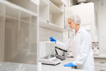 woman with sulphuric acid and scale at laboratory