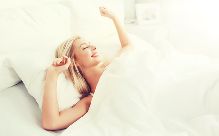 young woman stretching in bed at home bedroom Stock Photo