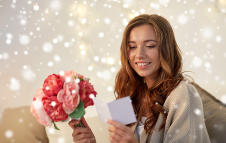 happy woman with flowers and greeting card at home Stock Photo