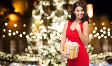 busty: gente, vacaciones y concepto de celebración - hermosa mujer sexy en vestido rojo con caja de regalo sobre fondo de árbol de Navidad Foto de archivo