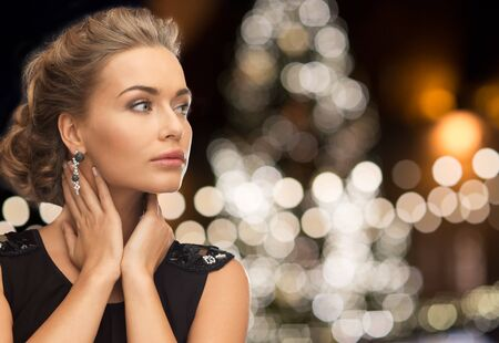 femme fatale: jewelry, holidays, luxury and people concept - beautiful woman in black wearing earrings over christmas tree lights background