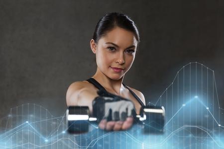 フィットネス、スポーツ、エクササイズ、トレーニング、人コンセプト - 若い女性のジムでダンベルで力こぶ 写真素材