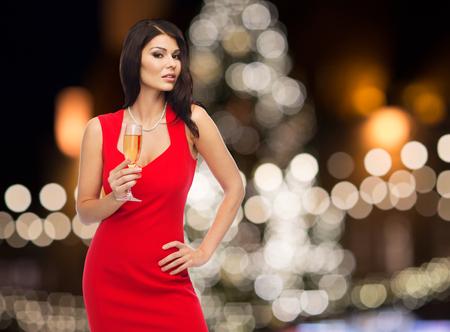 busty: personas, días de fiesta, la Navidad y la celebración de concepto - mujer atractiva en vestido rojo con el vidrio del champán
