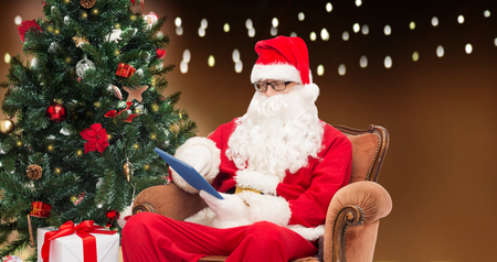 saint nicolas: technology, holidays and people concept - man in costume of santa claus with tablet pc computer, gift and christmas tree sitting in armchair over garland lights background