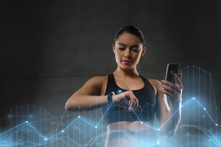sport, fitness, technology and people concept - young woman with heart-rate watch and smartphone in gym