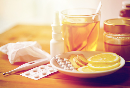 healthcare, traditional medicine and flu concept - tea cup with lemon, ginger, honey and pills on wooden table Stock Photo