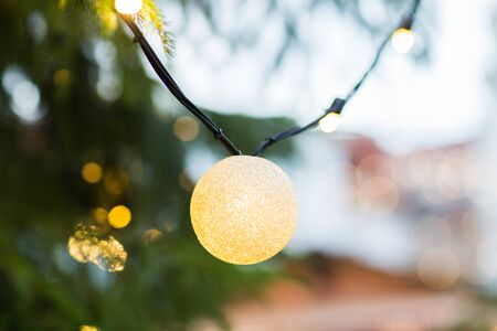holidays and decoration concept - close up of natural fir with christmas tree garland bulb outdoors