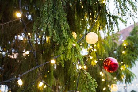 holidays and decoration concept - close up of natural fir with christmas tree toys and garlands outdoors Stock Photo