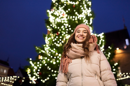 holidays and people concept - beautiful happy young woman at christmas tree in winter evening