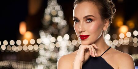 femme fatale: holidays and people concept - beautiful woman in black with red lips over christmas tree lights background Stock Photo