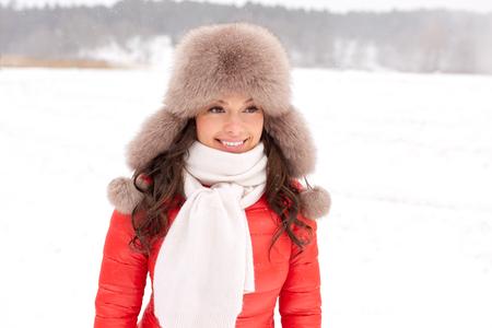 mensen, seizoen en vrije tijd concept - gelukkige vrouw in winter bont hoed buitenshuis Stockfoto