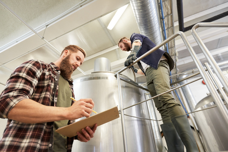production, business and people concept - men with clipboard working at brewery or non-alcoholic beer plant Stock Photo