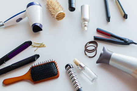 hair tools, beauty and hairdressing concept - hairdryers, irons, hot styling sprays and brushes on white background Stock Photo