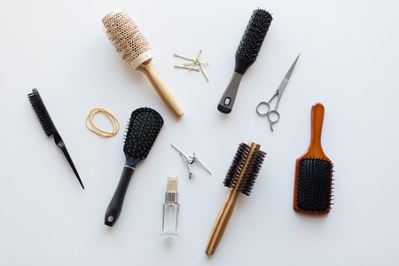 hair tools, beauty and hairdressing concept - scissors, different brushes, pins and styling spray on white background