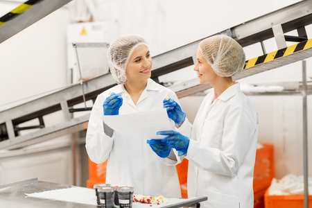 food production, industry and people concept - happy women technologists with clipboard tasting ice cream quality at factory Stockfoto