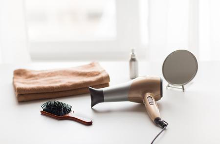 헤어 도구, 아름다움과 미용 개념 - 헤어 드라이어, 브러쉬, 미러 및 흰색 배경에 수건