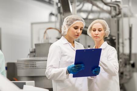 vervaardiging, industrie en mensenconcept - vrouwentechnologen met klembord bij de winkel van de roomijffabriek Stockfoto