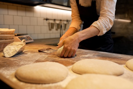 food cooking, baking and people concept - chef or baker making dough at bakery Banco de Imagens