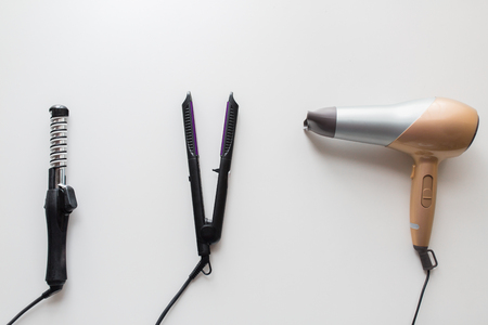 herramientas para el cabello, la belleza y el concepto de peluquería - secador de pelo, styler caliente y rizador o pinzas sobre fondo blanco Foto de archivo