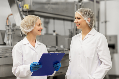 manufacture, industry and people concept - happy women technologists with clipboard at ice cream factory shop