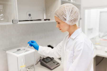 science, chemistry, industry and people concept - woman scientist or chemist adding sulphuric acid into flask on scale at laboratory