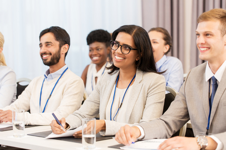 business and education concept - group of people at international conference or lecture