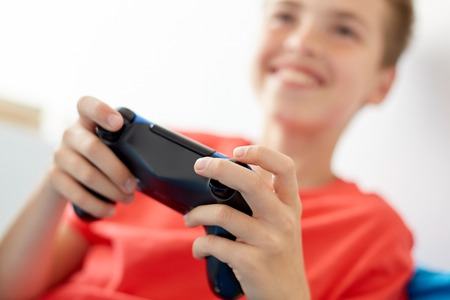 gaming, technology and people concept - close up of smiling boy with gamepad playing video game at home
