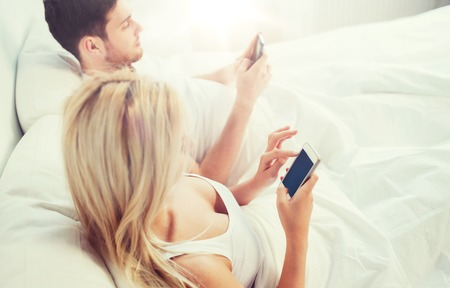 couple with smartphones in bed