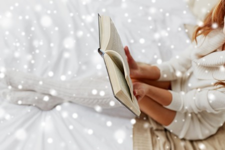 close up of young woman reading book at home