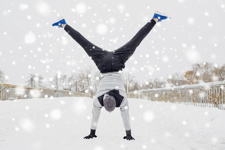 young man doing handstand in winter Stock Photo