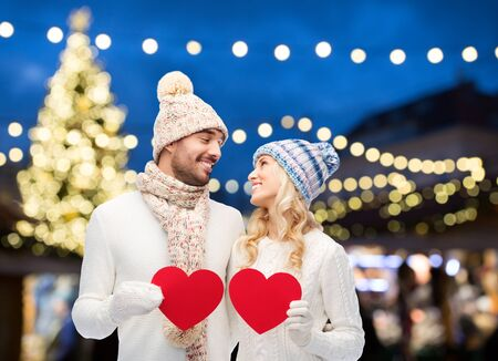 couple with red hearts over christmas tree lights Stock Photo