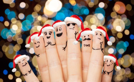 celebration smiley: close up of fingers in santa hats at christmas