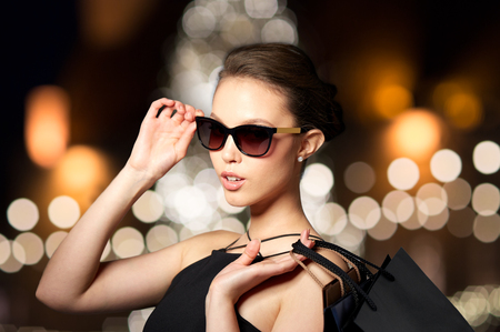 woman in shades with shopping bags at christmas