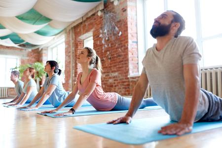 group of people doing yoga cobra pose at studio Foto de archivo